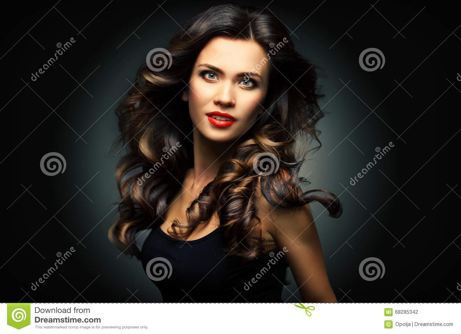 Beauté Woman modèle avec de longs cheveux onduleux de Brown Cheveux sains et beau maquillage professionnel Lèvres rouges et yeux