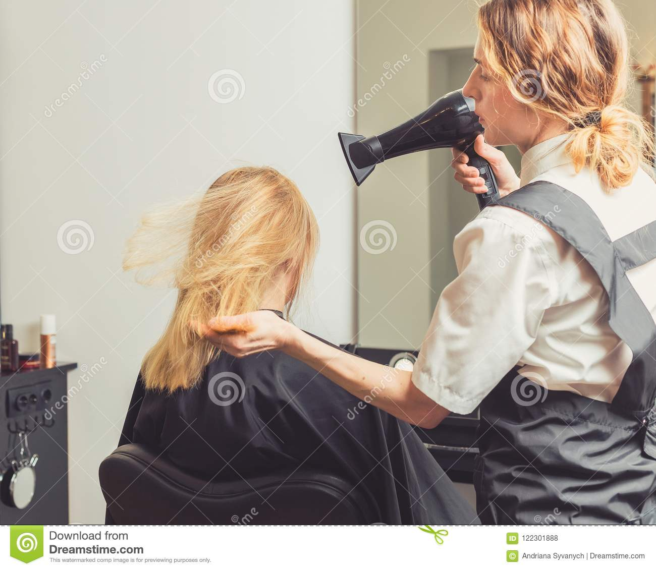 Beautician blow dry woman`s hair at beauty salon