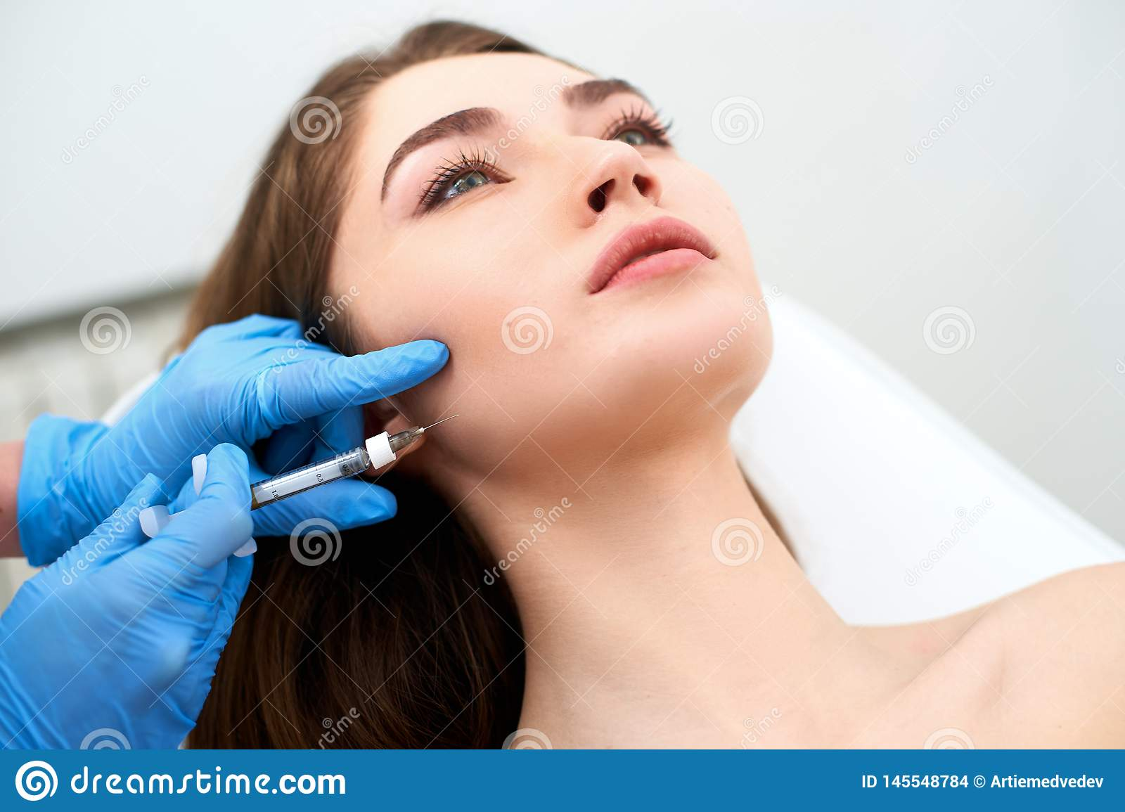 Beautician doctor with filler syringe making injection to jowls. Masseter lines reduction and face contouring therapy