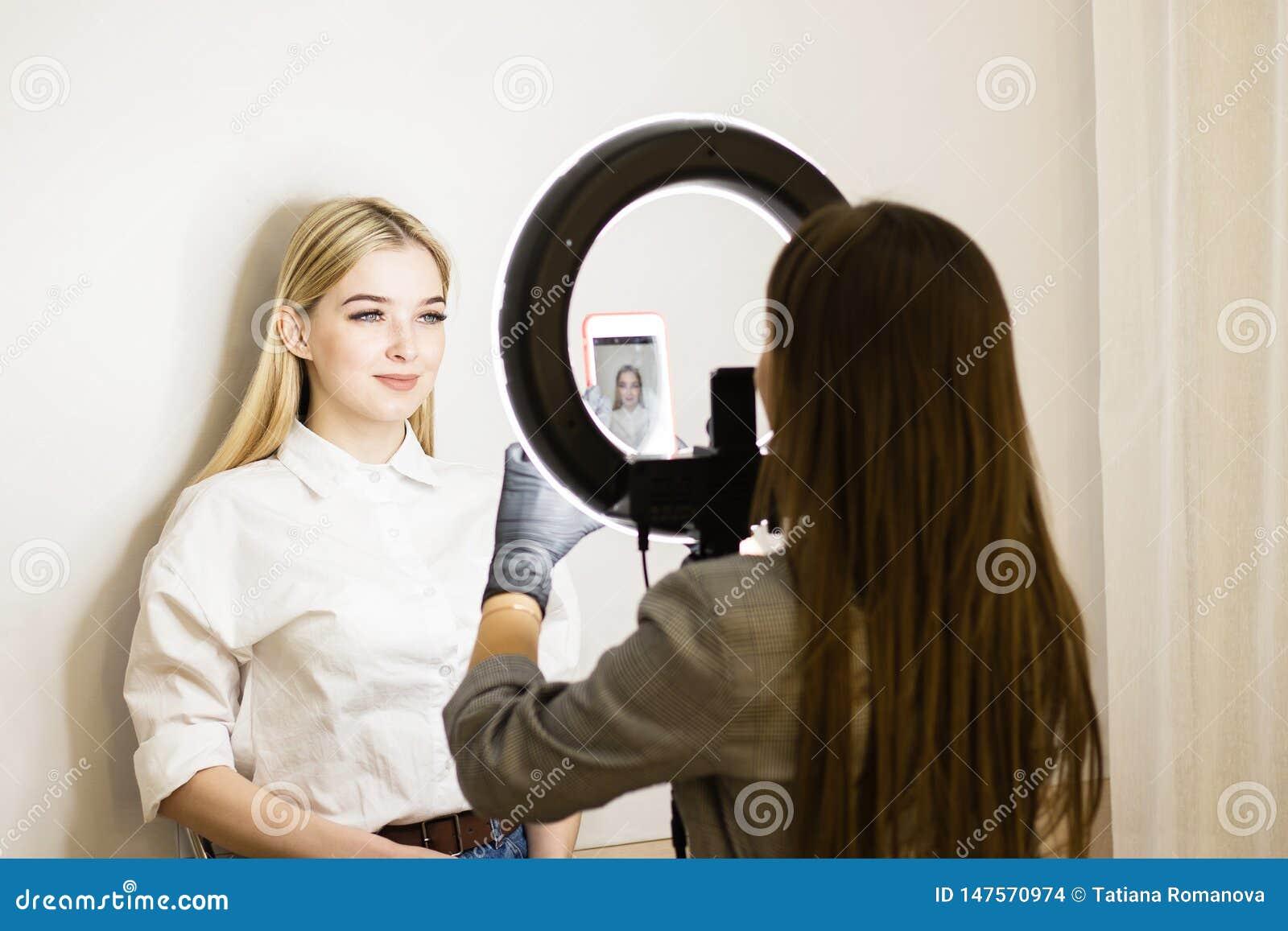 Beautician fotografuje jego pracę na telefonie komórkowym Dwa dziewczyny w piękno salonie Ringowa lampa dla makeup artystów Twarz