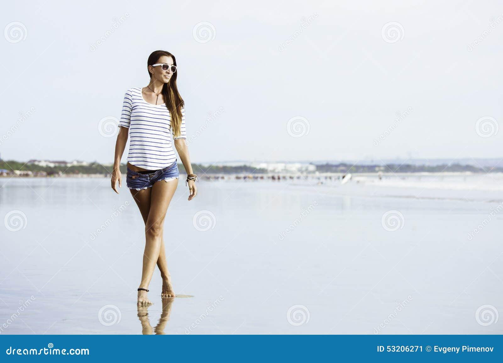 Beautifil młoda kobieta z odprowadzeniem wzdłuż plaży
