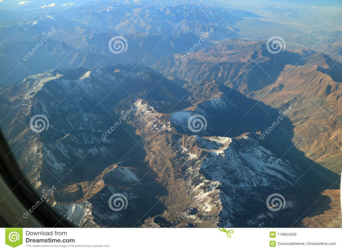 Beautiful aerial view of snow capped mountain range seen from airplane window