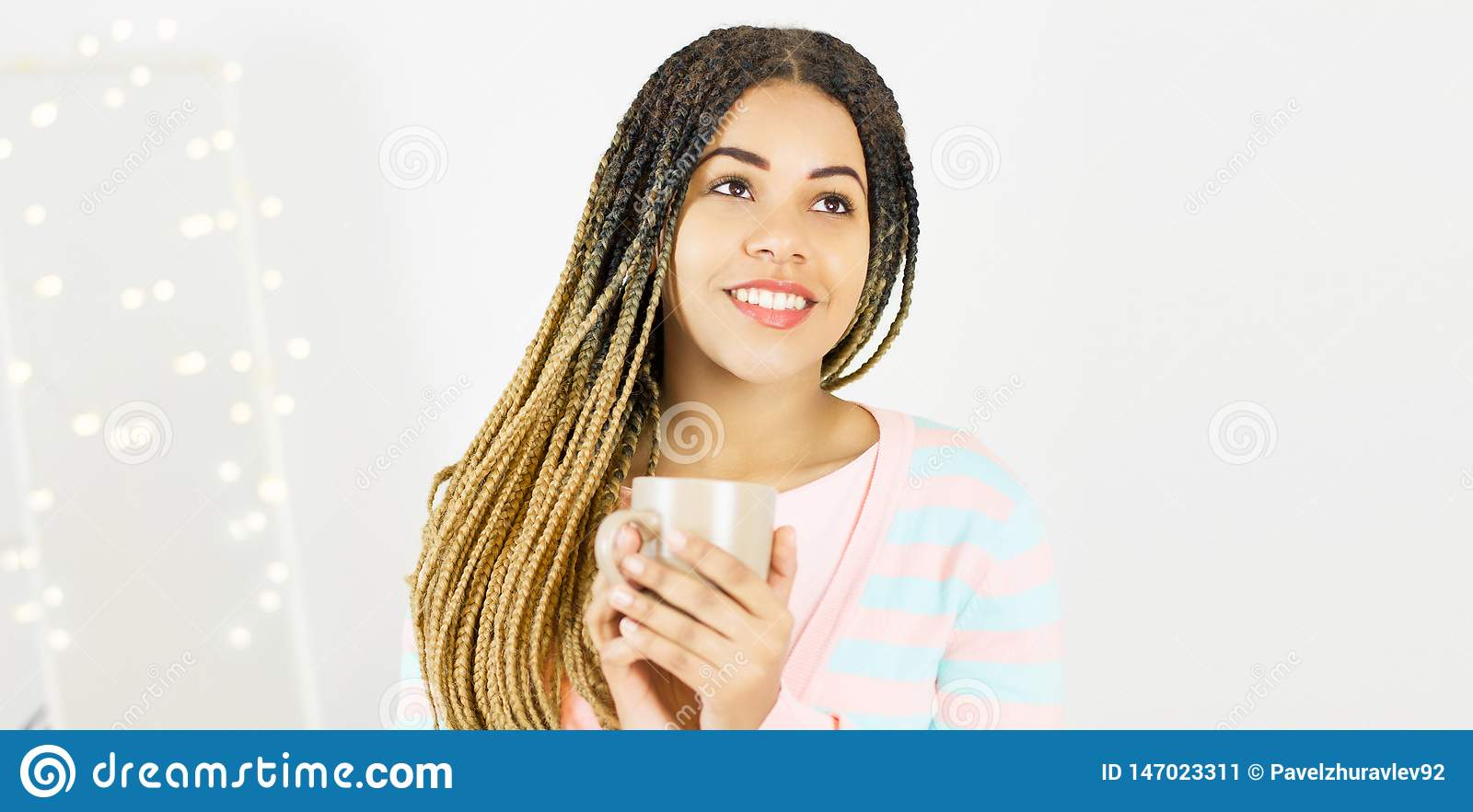 Beautiful african american girl with cup and afro hairstyle smiling