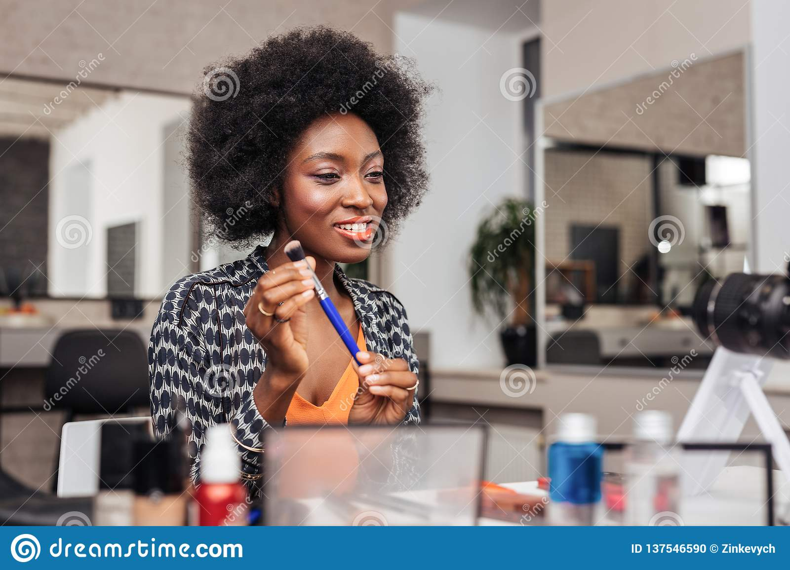 Beautiful african american woman with bright lipstick looking amused