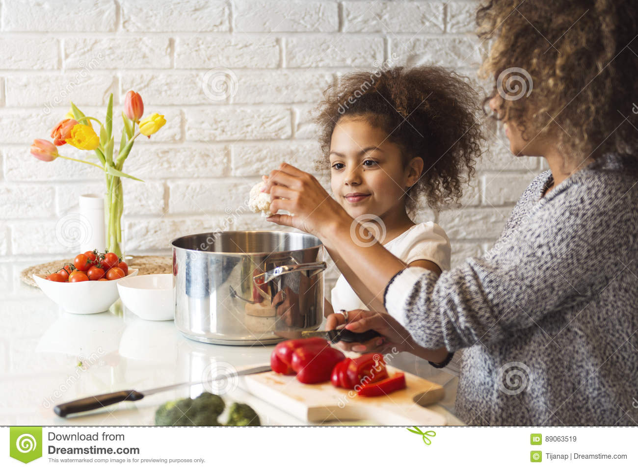 Beautiful African American woman and her daughter cooking