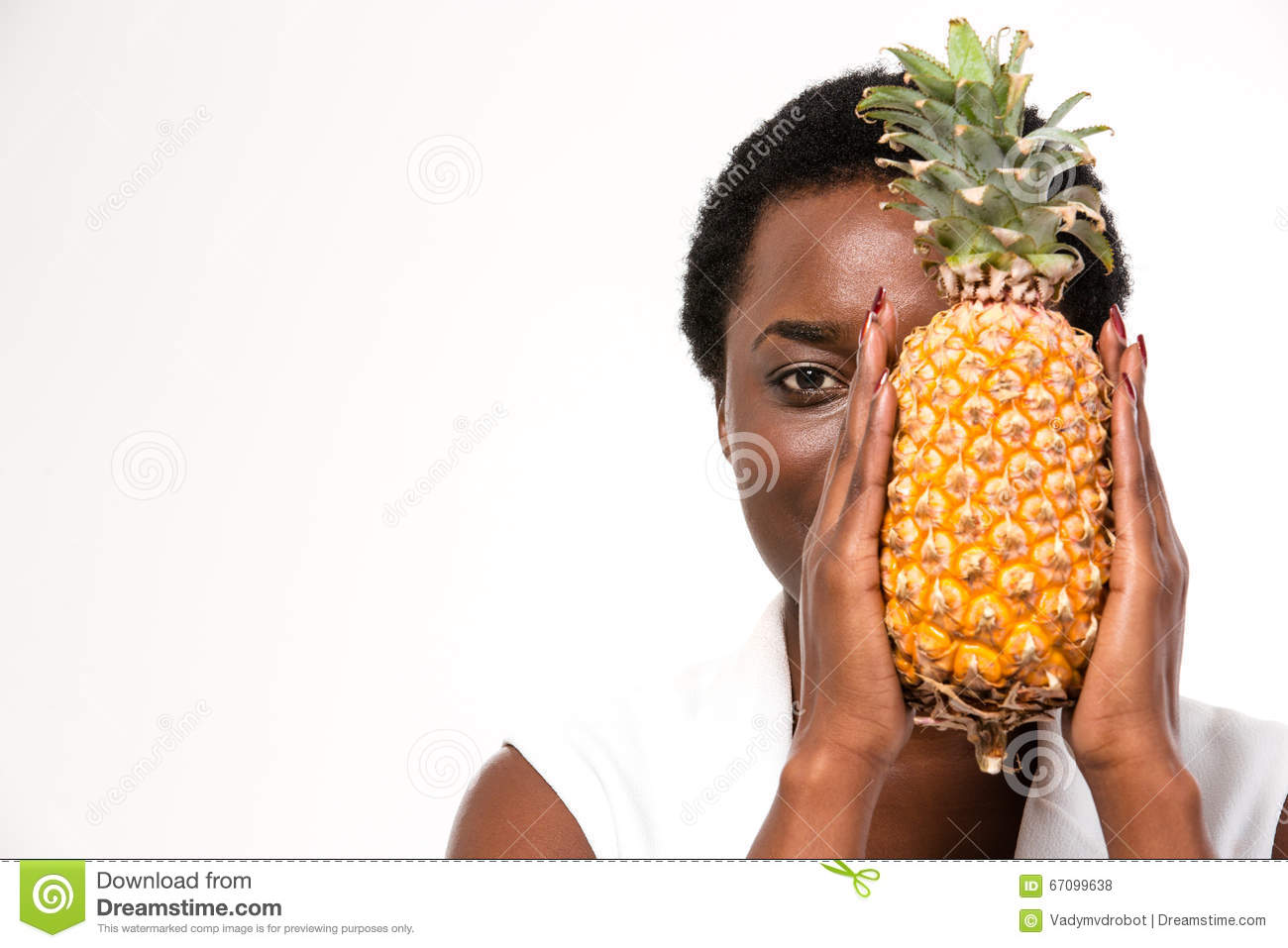 Beautiful african american woman hiding half of face with pineapple