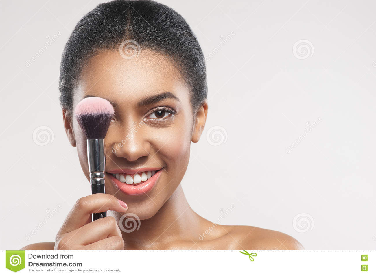 Beautiful african girl applying blush on skin