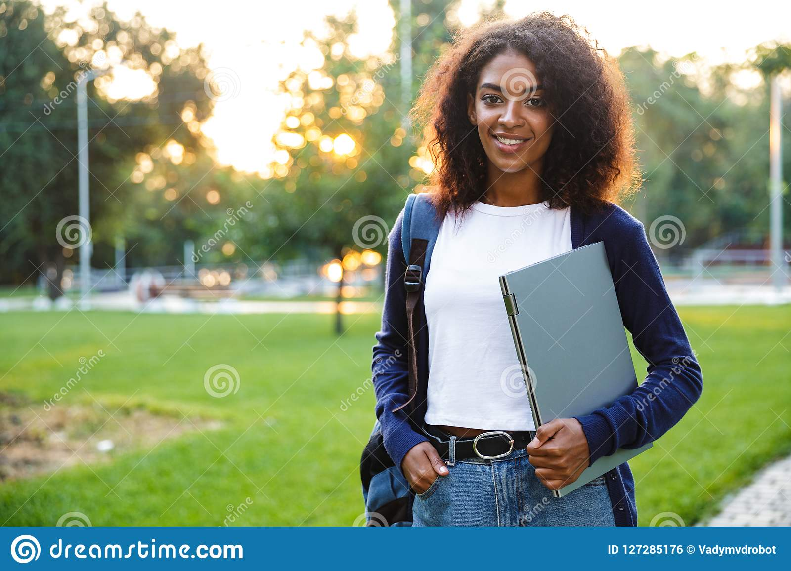 Beautiful african woman student walking in the park holding laptop computer.