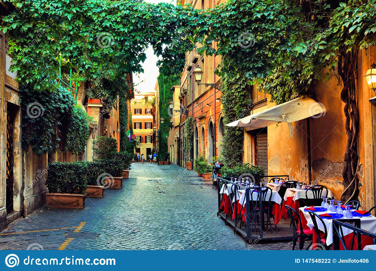 Old street in Rome with leafy vines and cafe tables, Italy