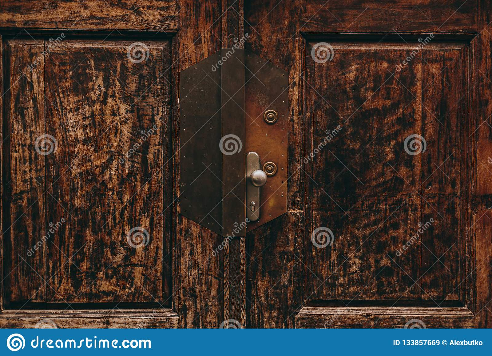 Beautiful antique wooden doors in Italy with metal handles