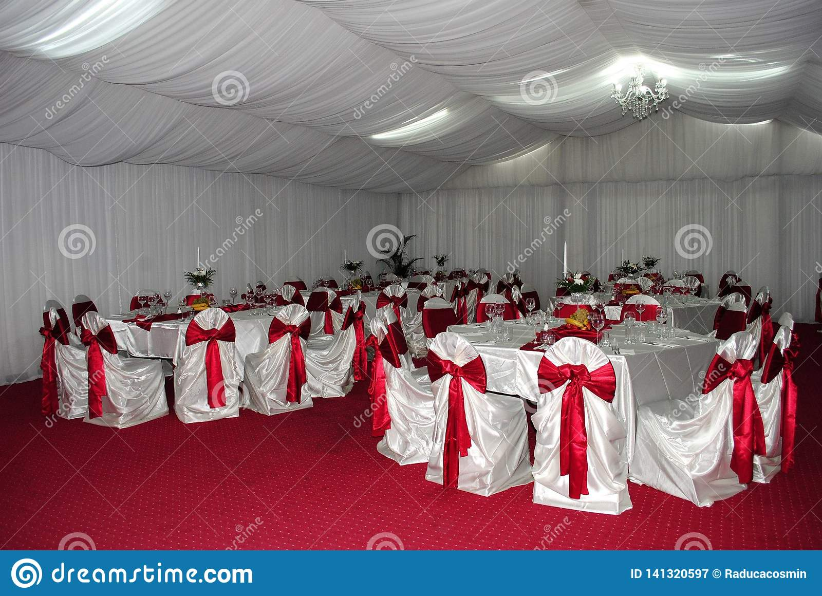 Wedding arrangement with white and red chairs awaiting guests