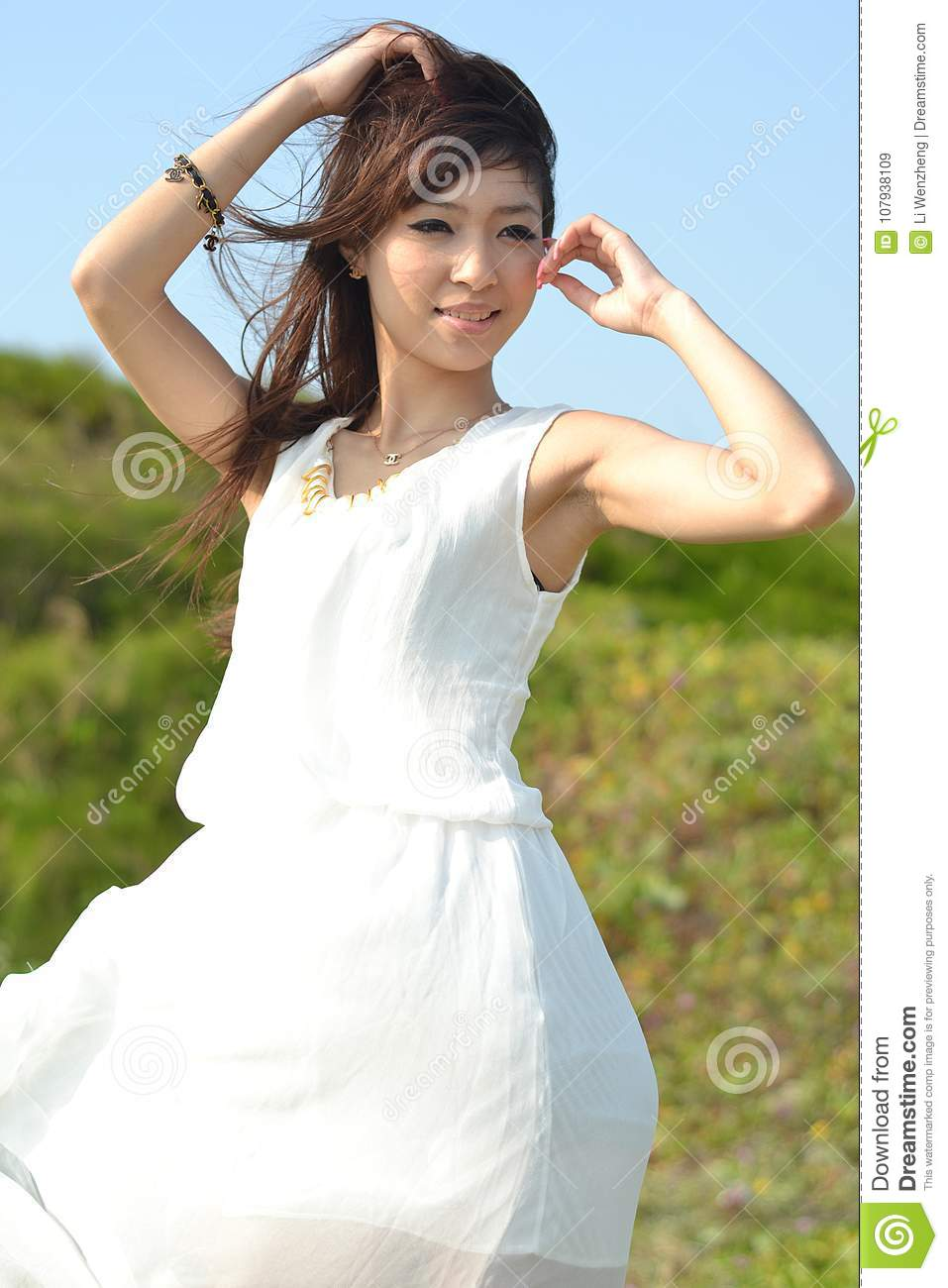 Beautiful asian girl playing on the beach, a white dress, sweet smile, the  sea breeze blowing hair