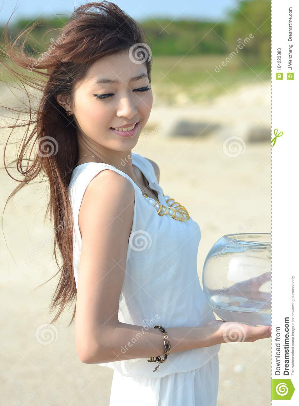 Beautiful Asian girl in a white dress at the beach, the sea breeze blowing  hair, beautiful young, pure