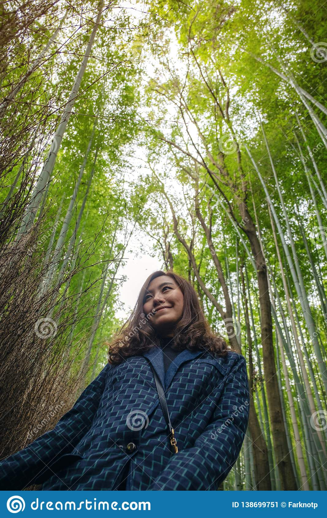 A woman with bamboo forest in background