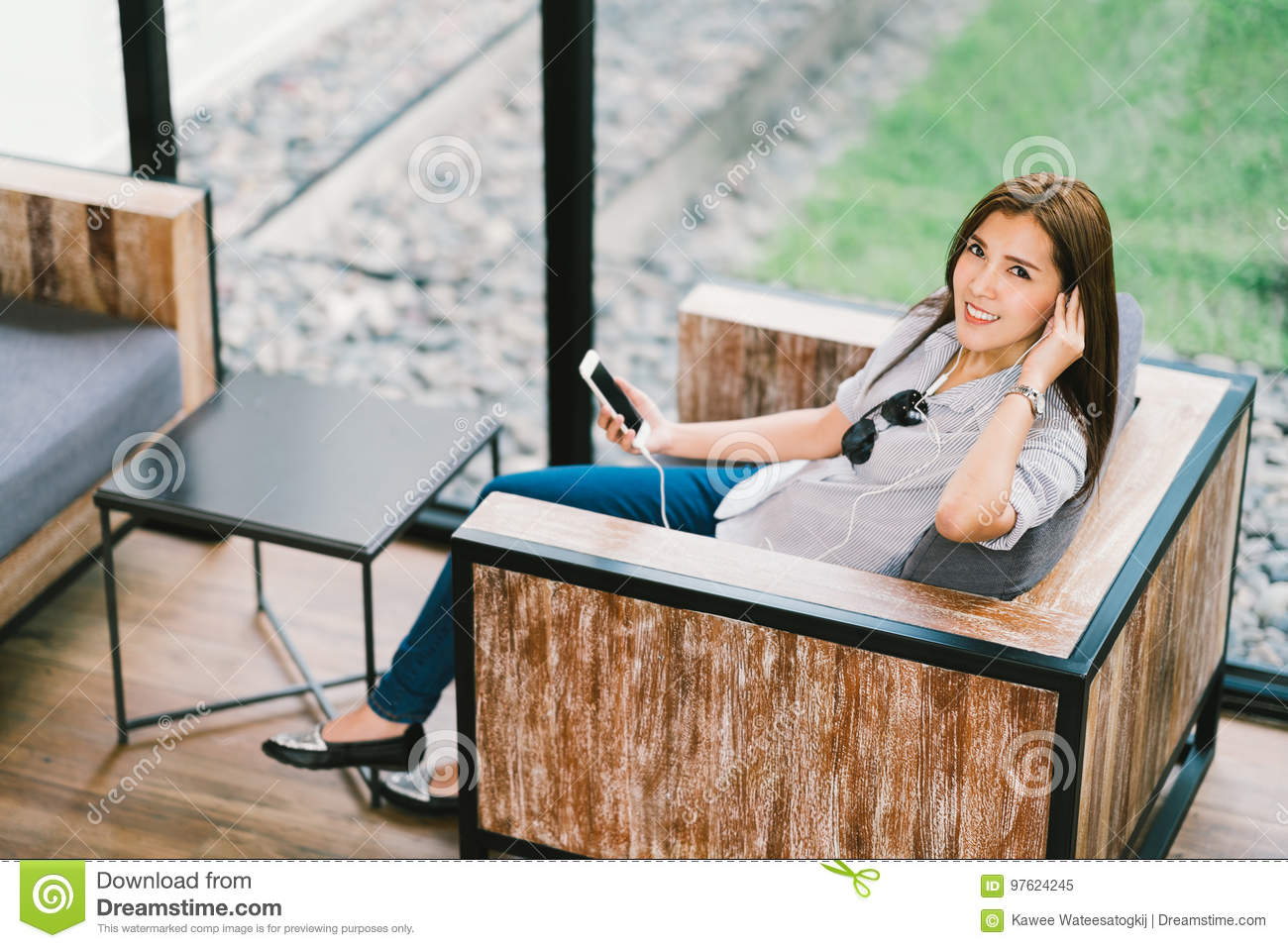 Beautiful Asian woman listening to music using smartphone, sitting in cafe or coffee shop. Relaxing hobby activity concept