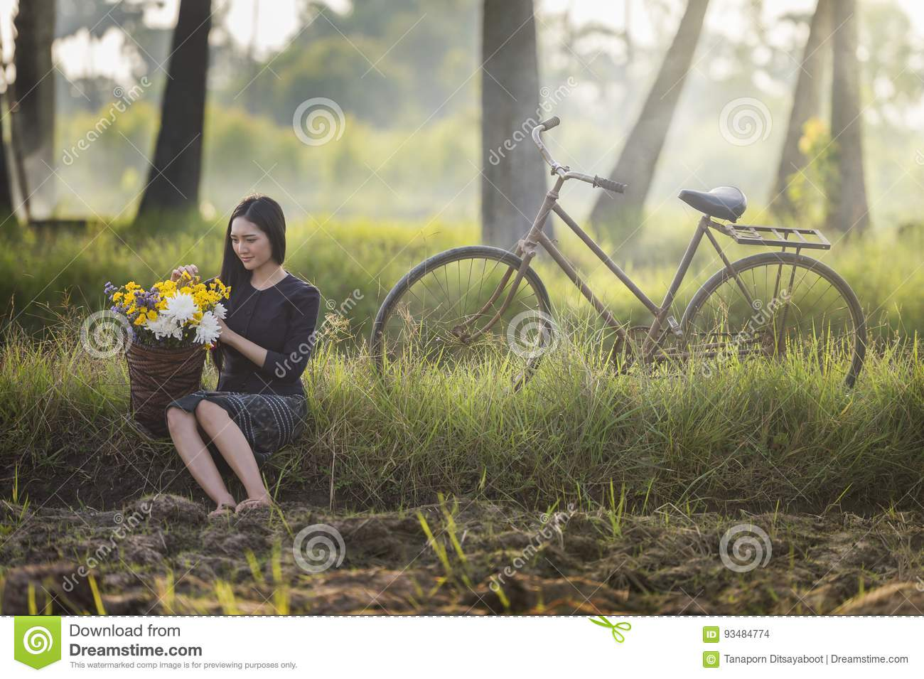 Beautiful Asian woman in local traditional dress with old bicycle and flower basket on the green summer field.