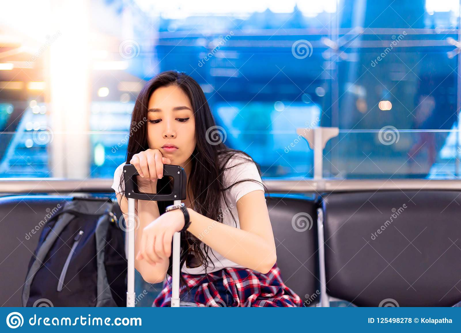 Beautiful asian woman looks at wristwatch for checking the time.