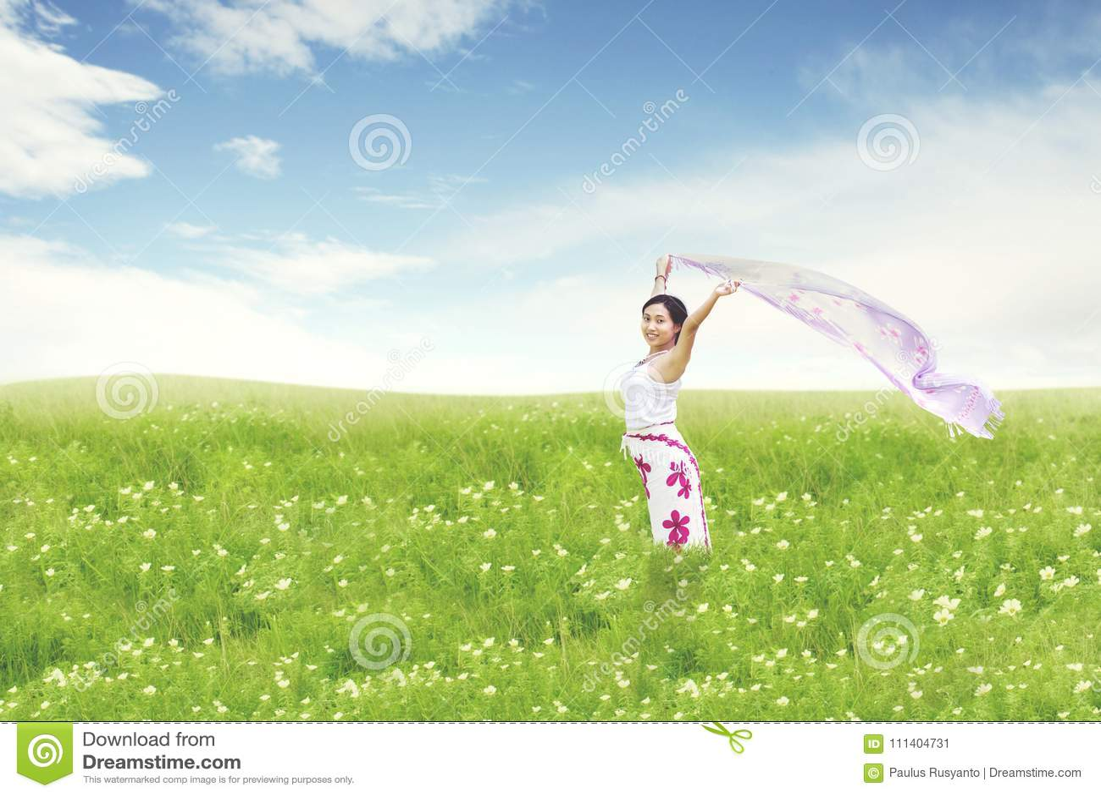 Beautiful asian woman running on field