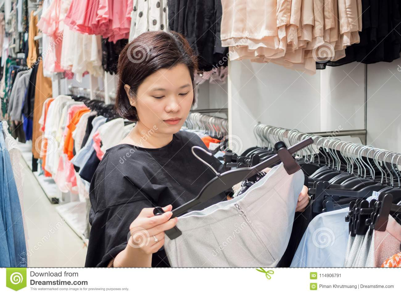 Asian woman shopping in fashion clothes store