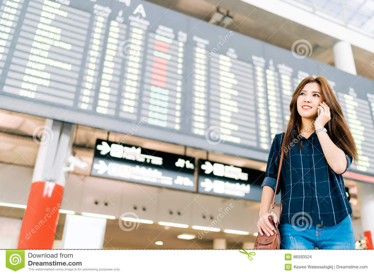 Beautiful Asian woman traveler on mobile phone call at flight information board in airport, holiday vacation travel concept