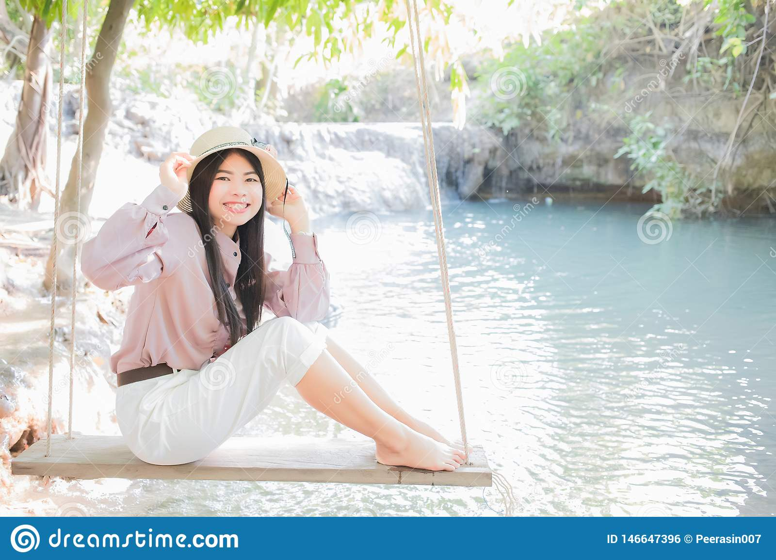 Beautiful Asian women, Thai people, wearing pink casual clothes with a refreshing and smiling face are sitting on the swings.