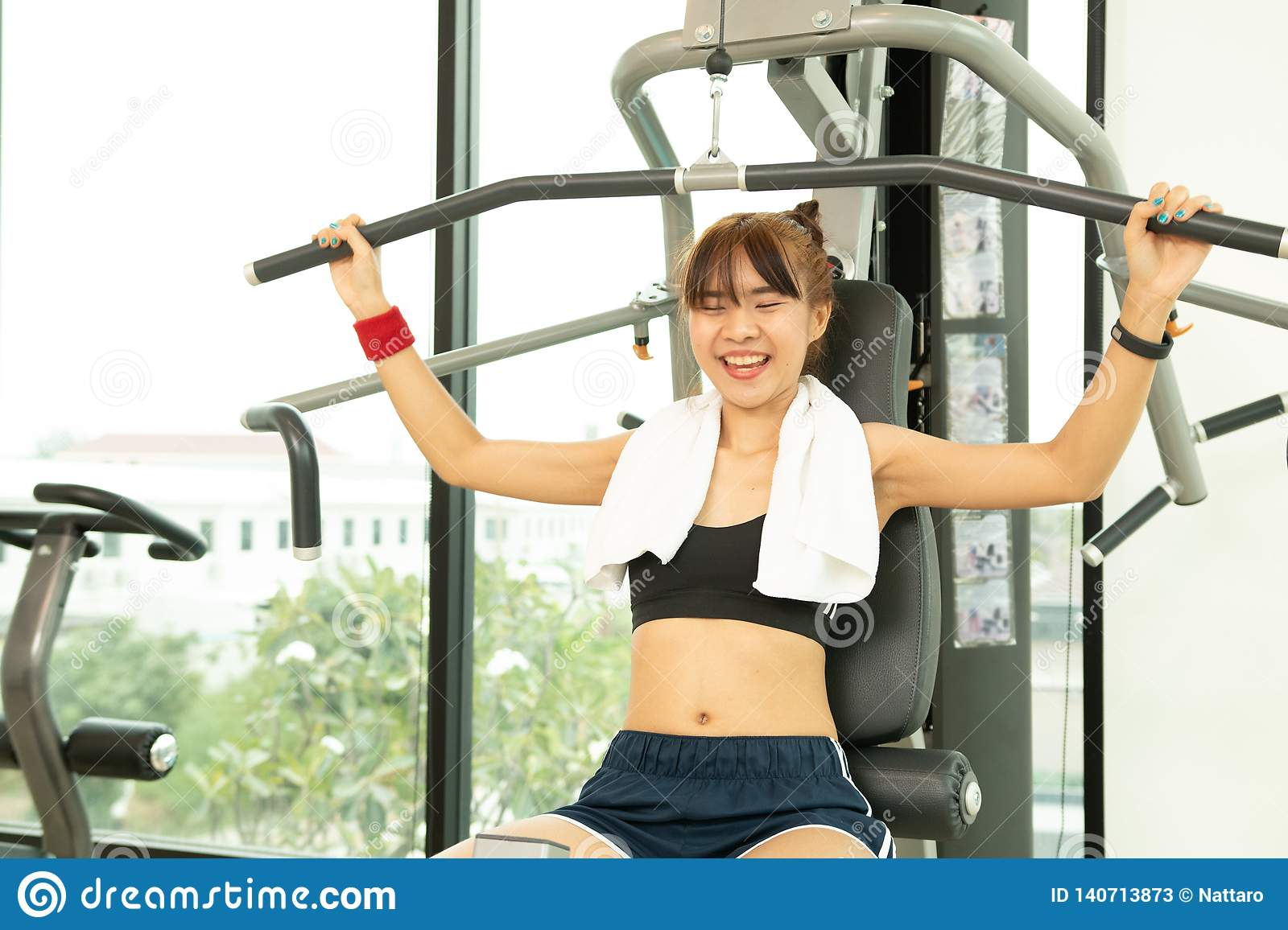 Beautiful Asians young fitness woman lifting barbell. Sporty woman lifting weights. Fit girl exercising building muscles. Fitness