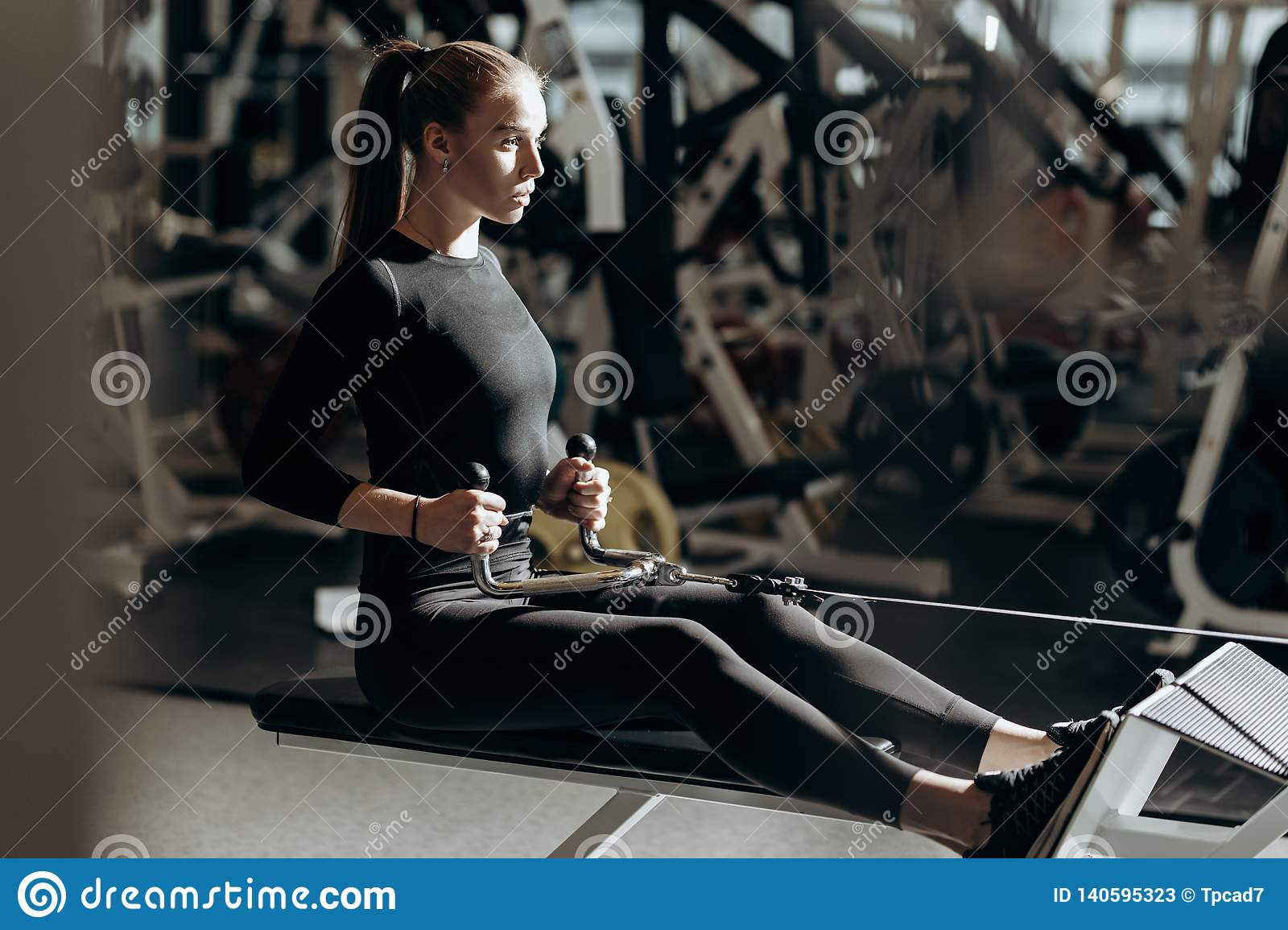 The beautiful athletic girl dressed dressed in a black sportswear is doing sport exercises with equipment on the bench
