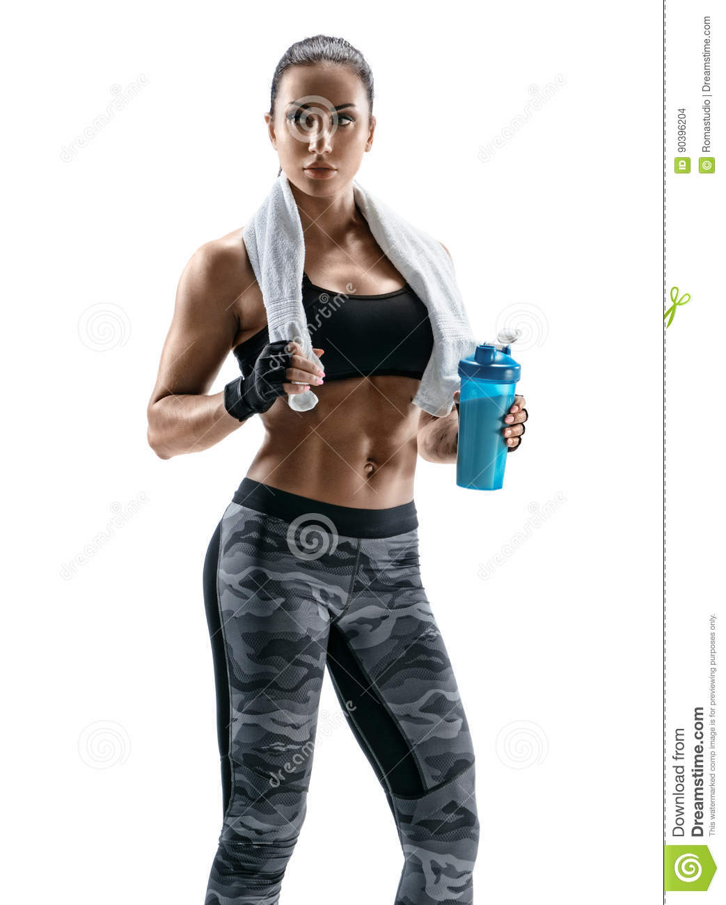 Beautiful athletic woman with towel on shoulders holding protein cocktail in shaker