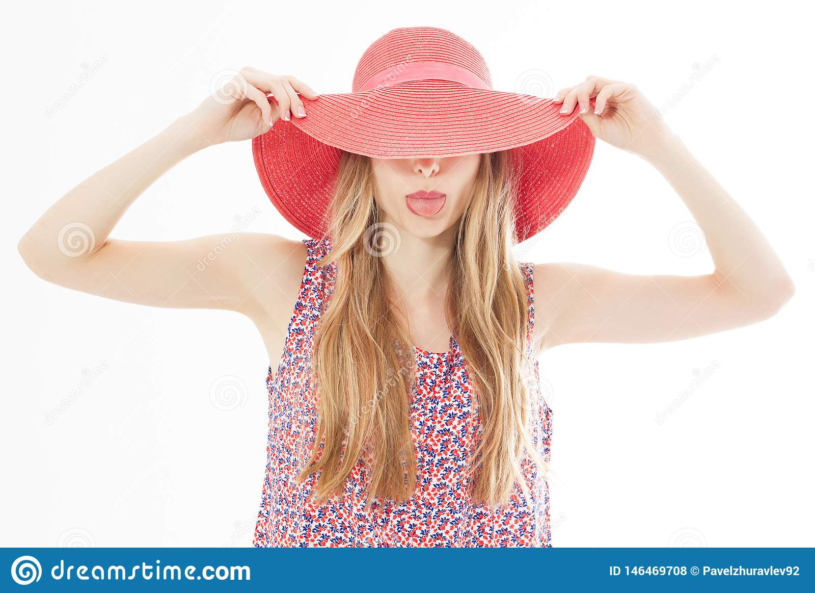 Beautiful attractive girl hides her face behind her summer hat and shows her tongue isolated over white
