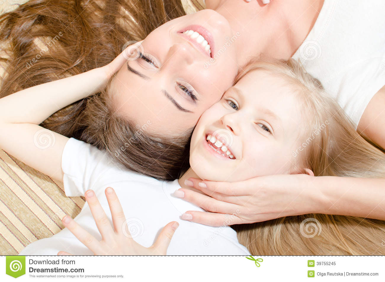 Beautiful attractive mother or sister with child girl lying face to face happy smiling & looking at camera