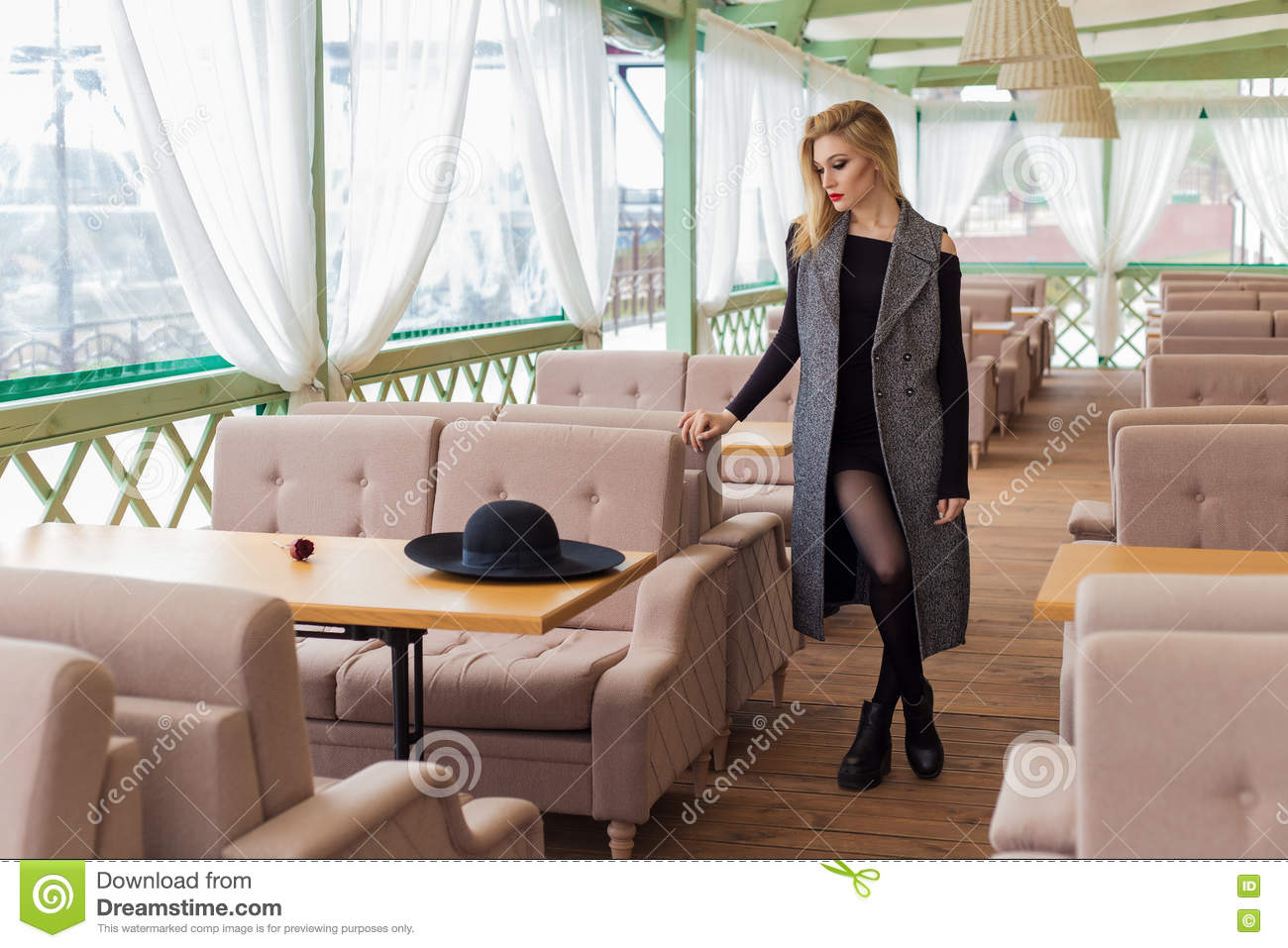 Beautiful attractive blond girl in a cafe in a black hat and coat with trendy makeup smokey eyes
