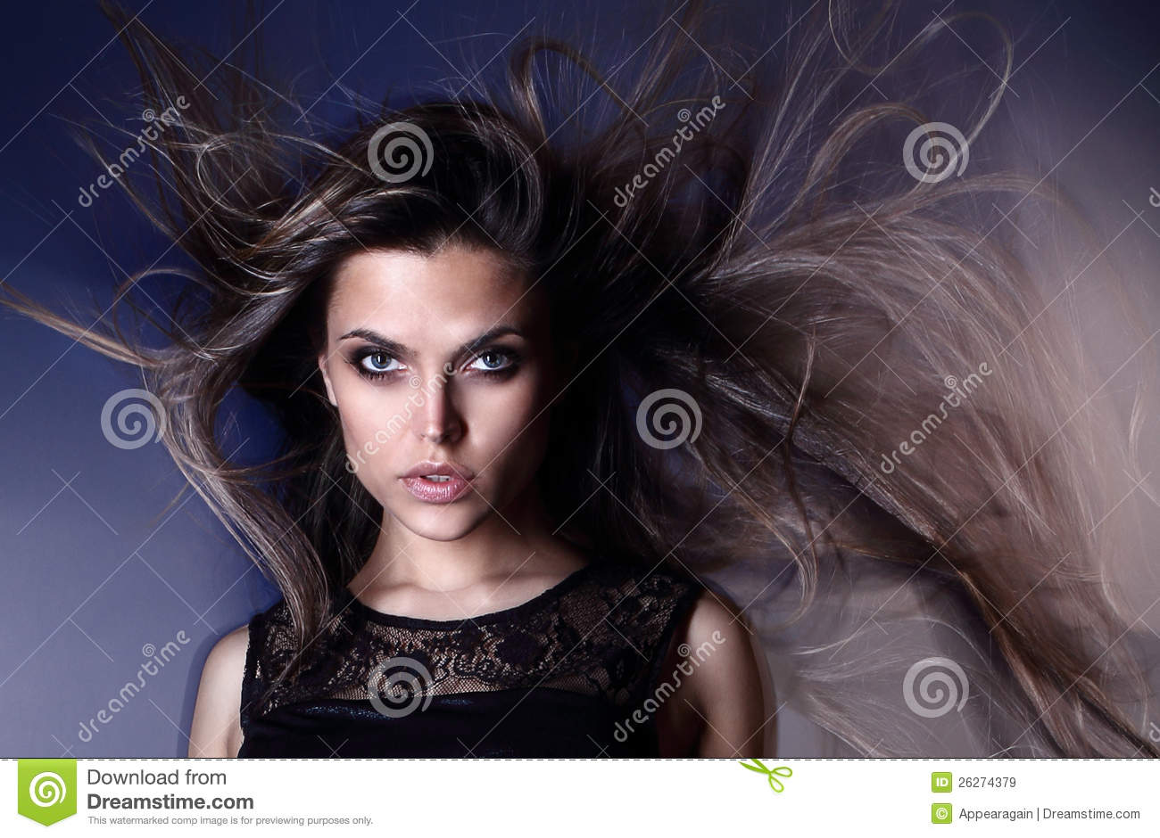 Beautiful attractive young Brazilian fashion model with hair blown by the air studio shot