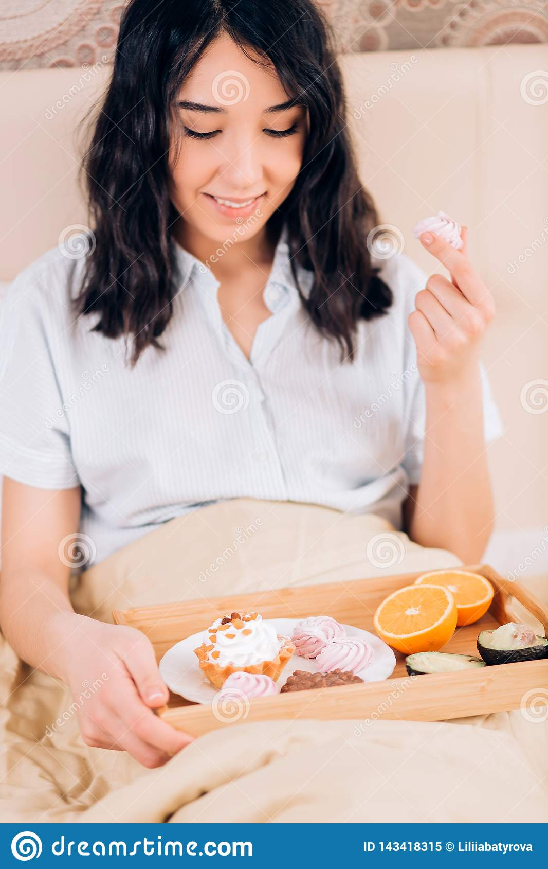 Beautiful awesome dark haired woman having tasty breakfast in bed at her cozy bedroom. Side view photo of young girl in blue