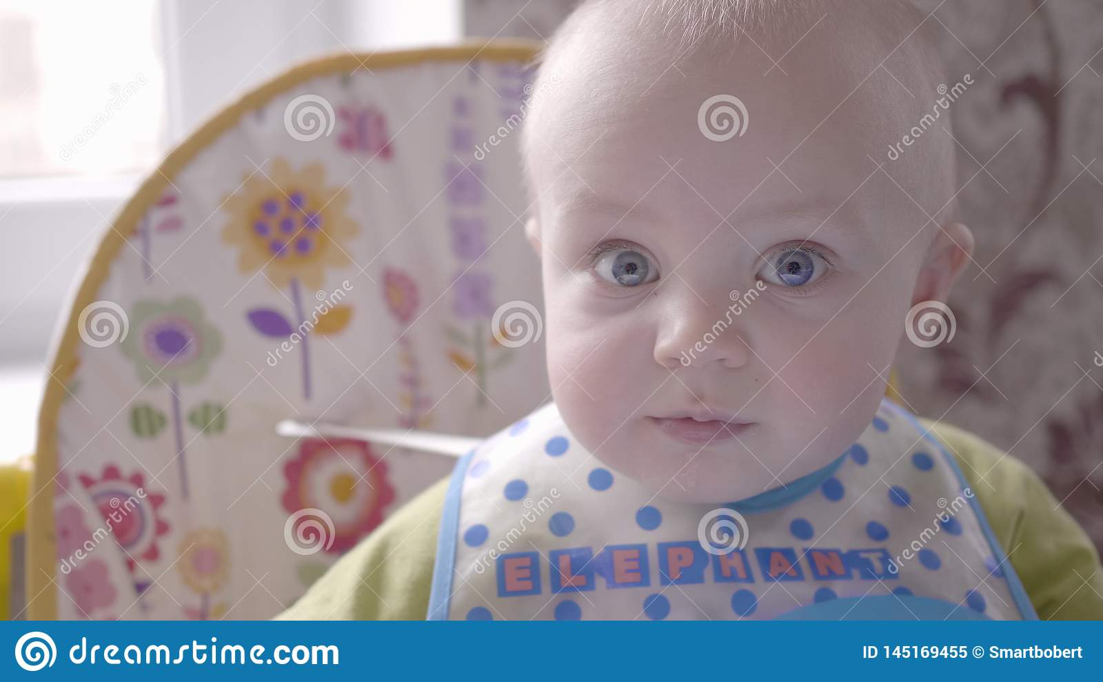 Beautiful baby boy at the table take a cookie in his hand, eating it, watching into the camera and babbling close up