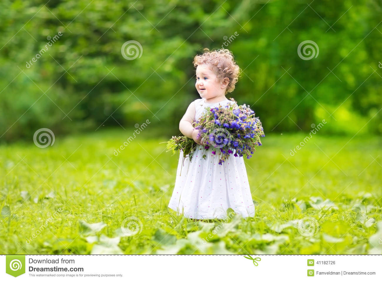 beautiful baby girl carrying flowers in a garden stock photo - image
