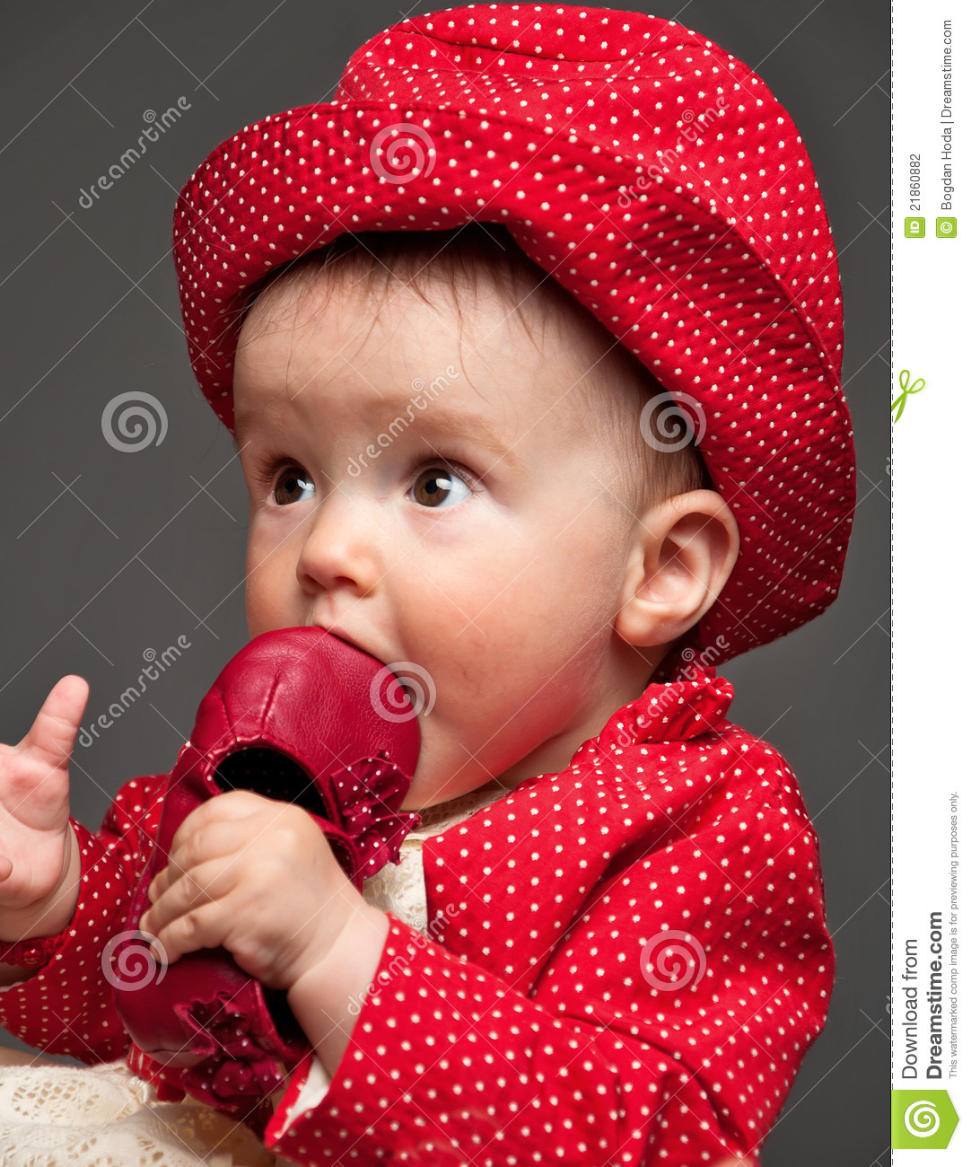 beautiful baby girl dressed in a red dress eating stock photo