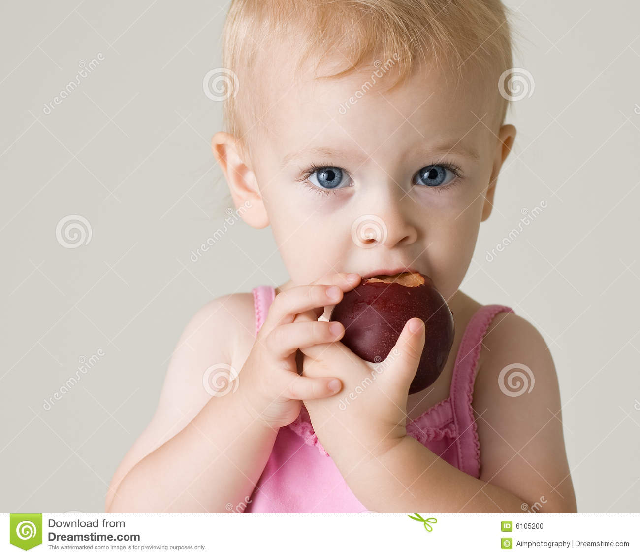 Color portrait of a cute baby girl enjoying eating a fresh plum