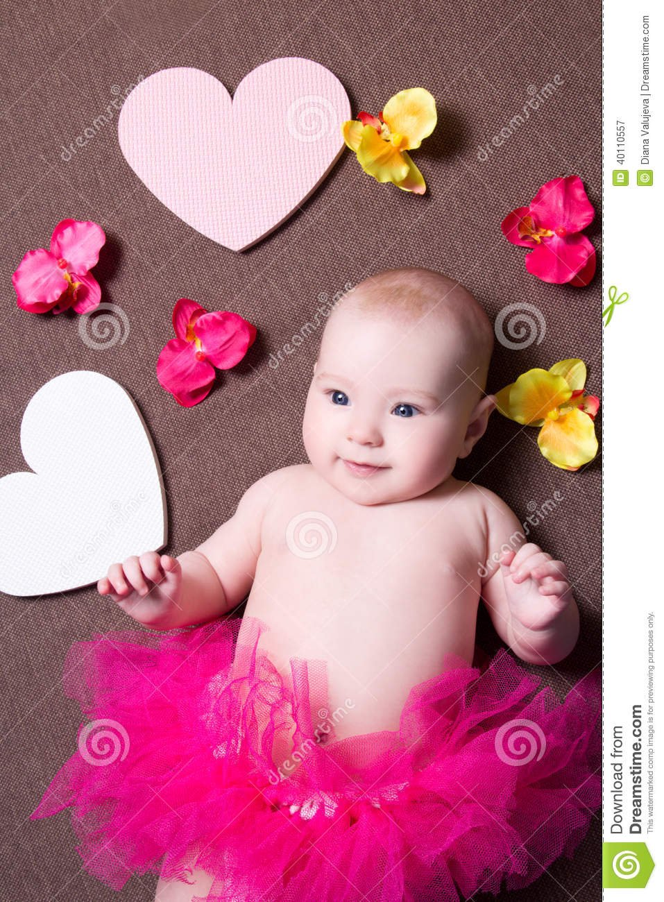 Beautiful baby girl in pink skirt lying with hearts and flowers royalty free stock photo izmirmasajfo Choice Image