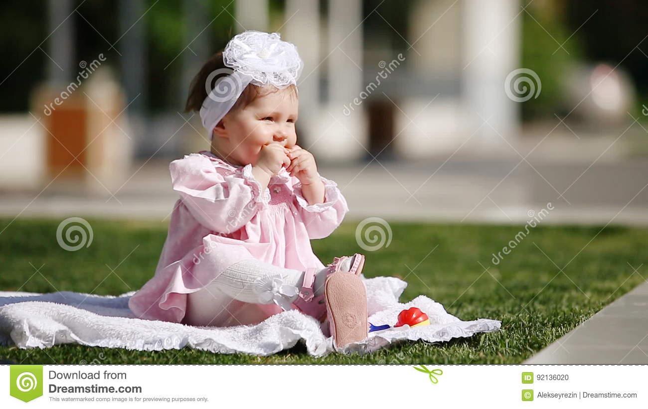 3a8484124ca6 Beautiful Baby-girl Seating On The Green Grass And Eating Bake In The Park.  Stock Footage - Video of daylight, park: 92136020
