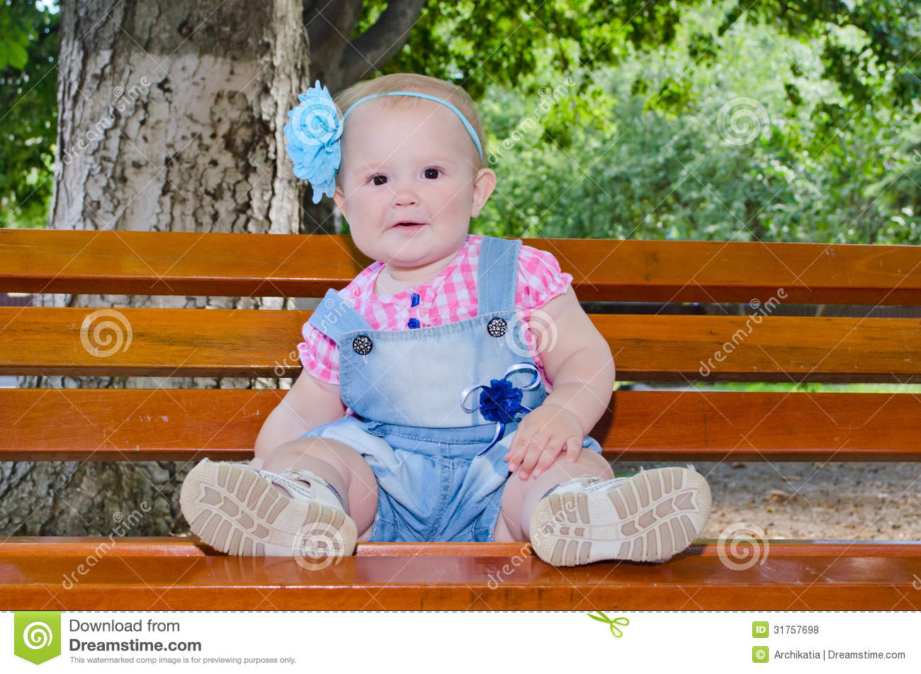Beautiful Baby Girl Sitting On The Bench Royalty Free