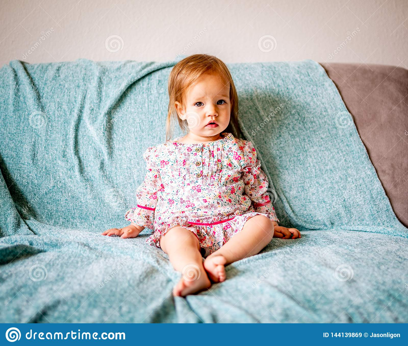 Adorable Baby Girl Sits on Couch