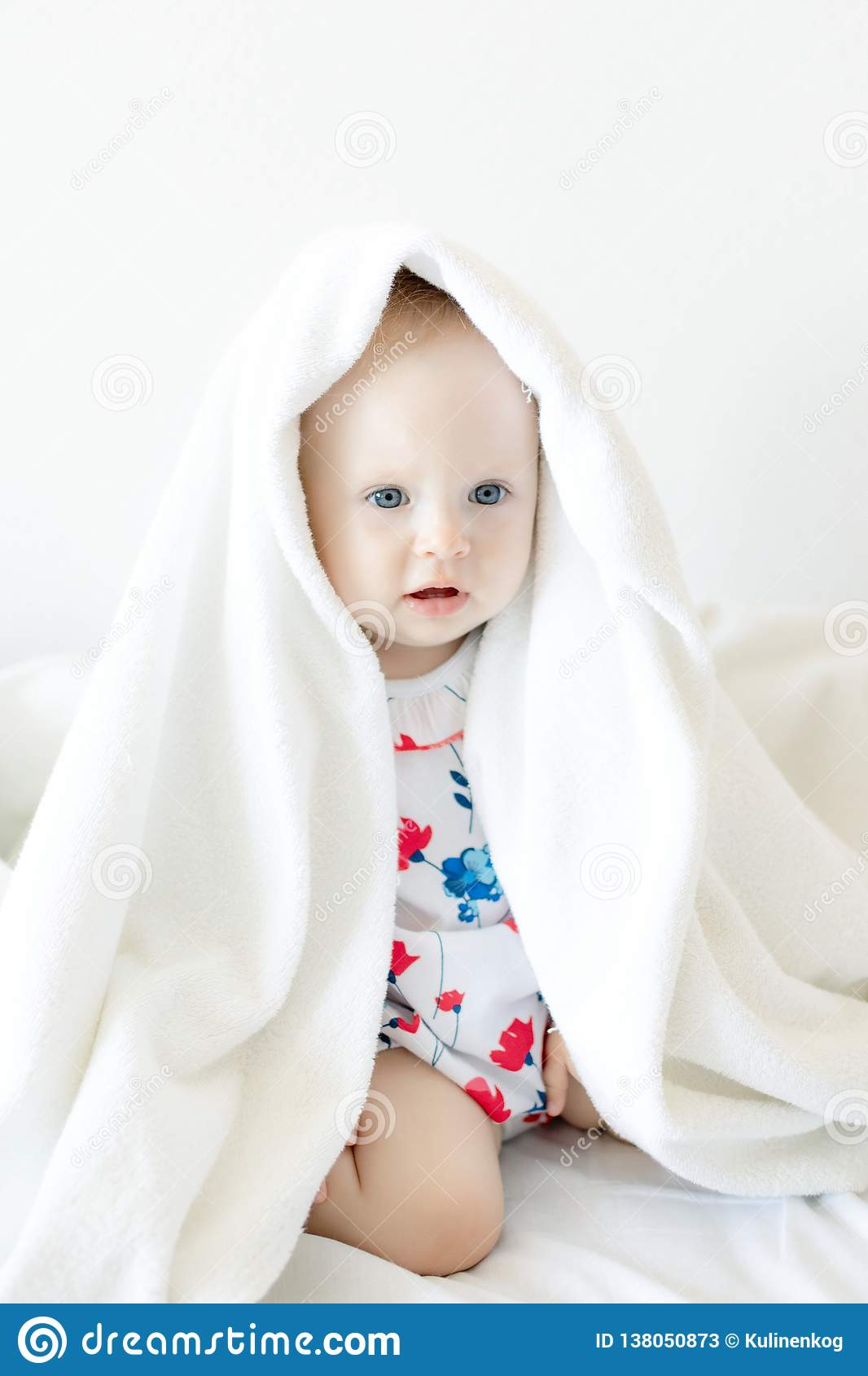 Beautiful baby kid Peeps out from under the sheets and fervently plays posing for the camera