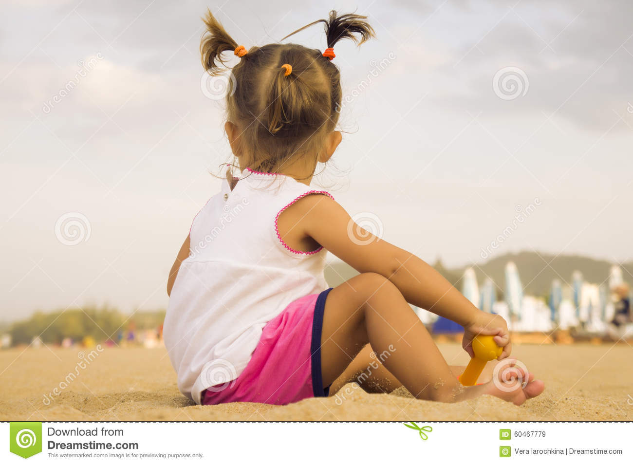 Beautiful baby sitting with his back to the camera and playing with toy rake in the sand on the beach.