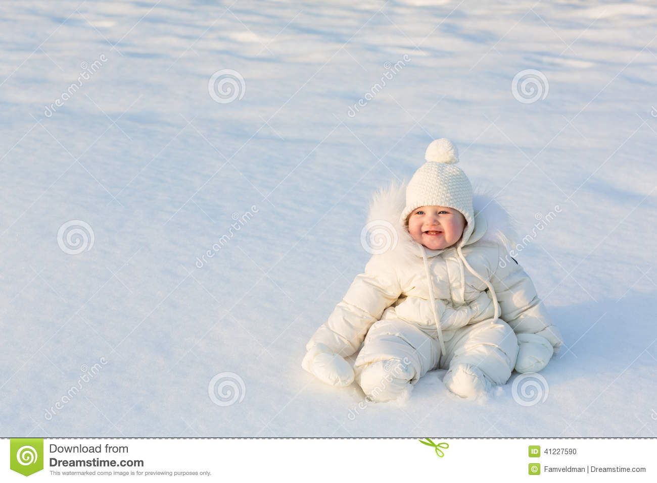 Beautiful Baby In A White Snow Suit Sitting On Fresh Snow