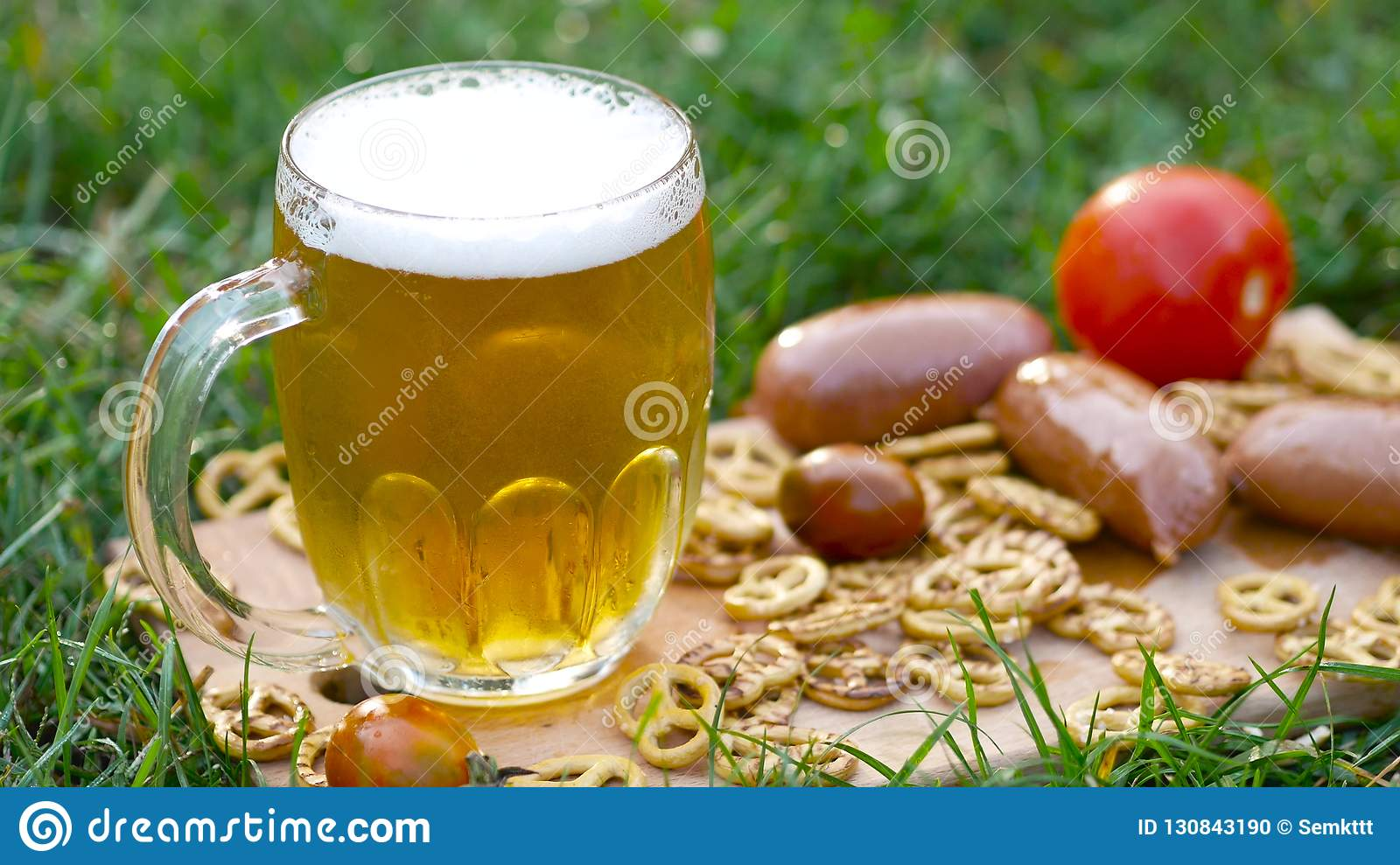 Glass of beer, pretzel and sausages