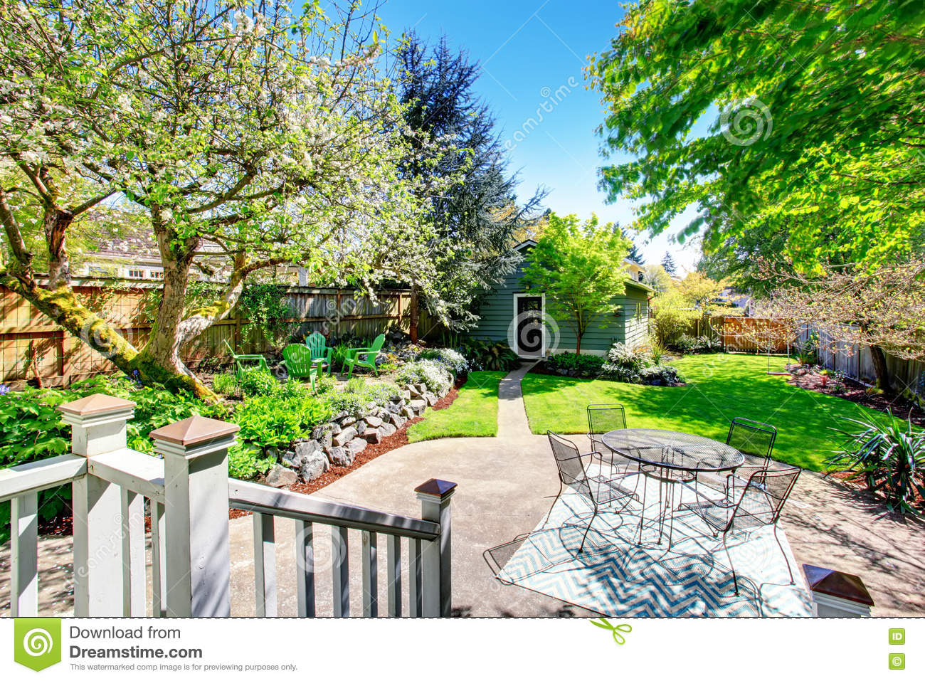 beautiful backyard view with two patio areas and blooming trees