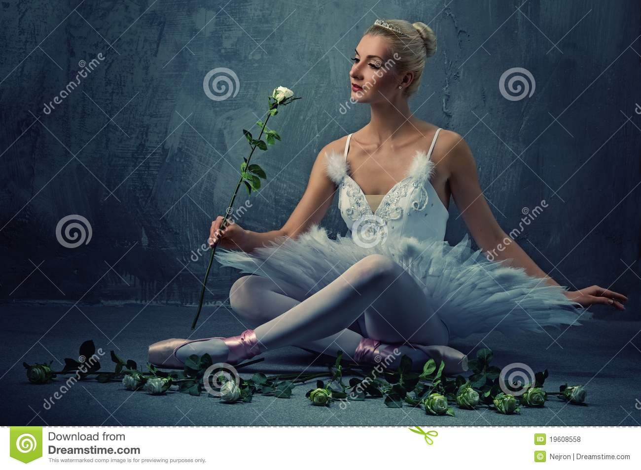 Beautiful ballet dancer with a white roses.