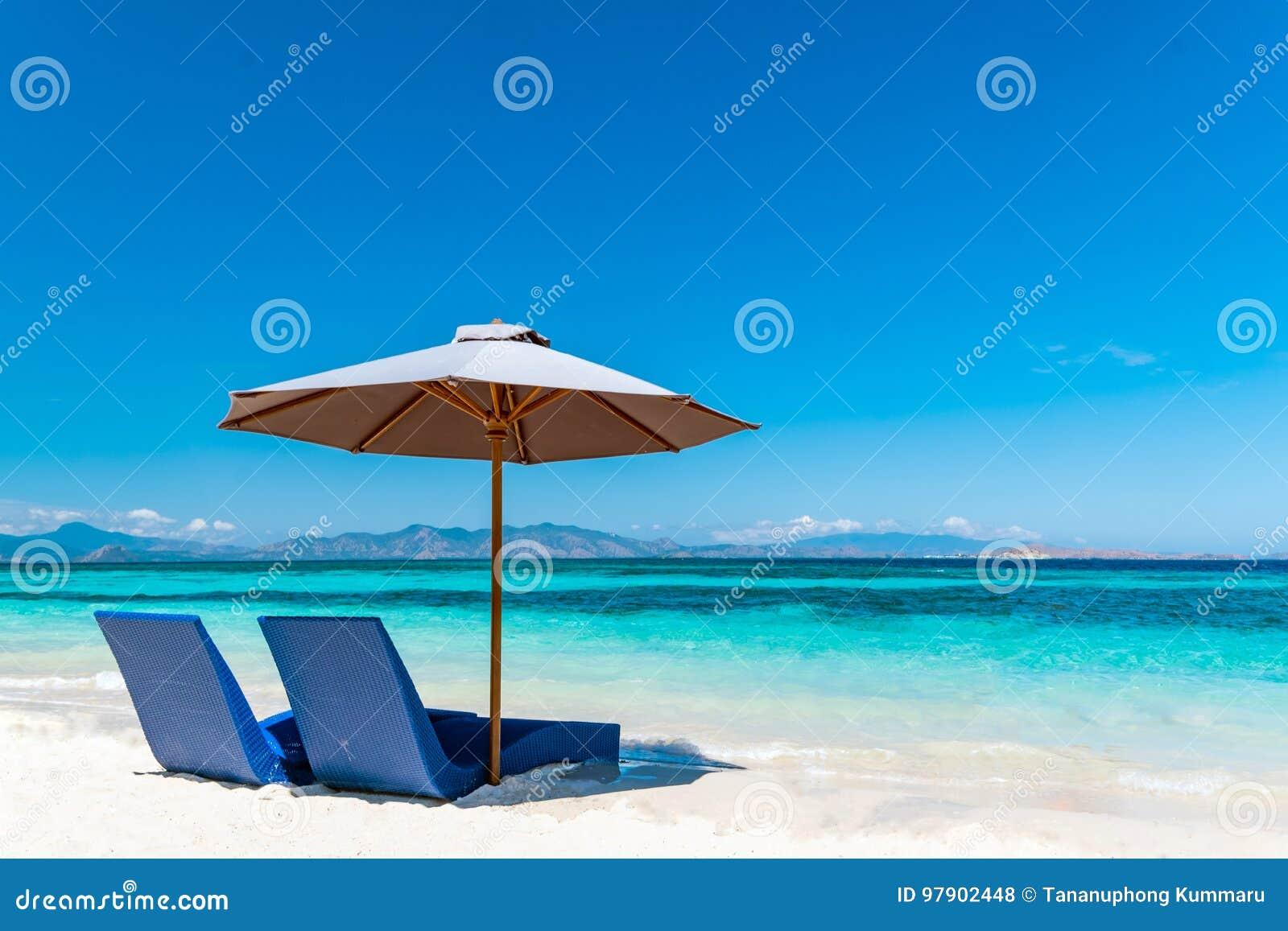 Beautiful beach. Sunbeds with umbrella on the sandy beach near the sea.