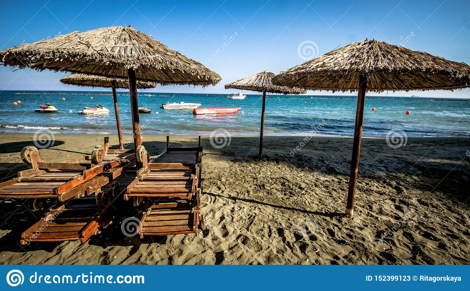 Beautiful beach. Sunbeds with umbrella on the sandy beach near the sea. Summer holiday and vacation concept. Inspirational tropica
