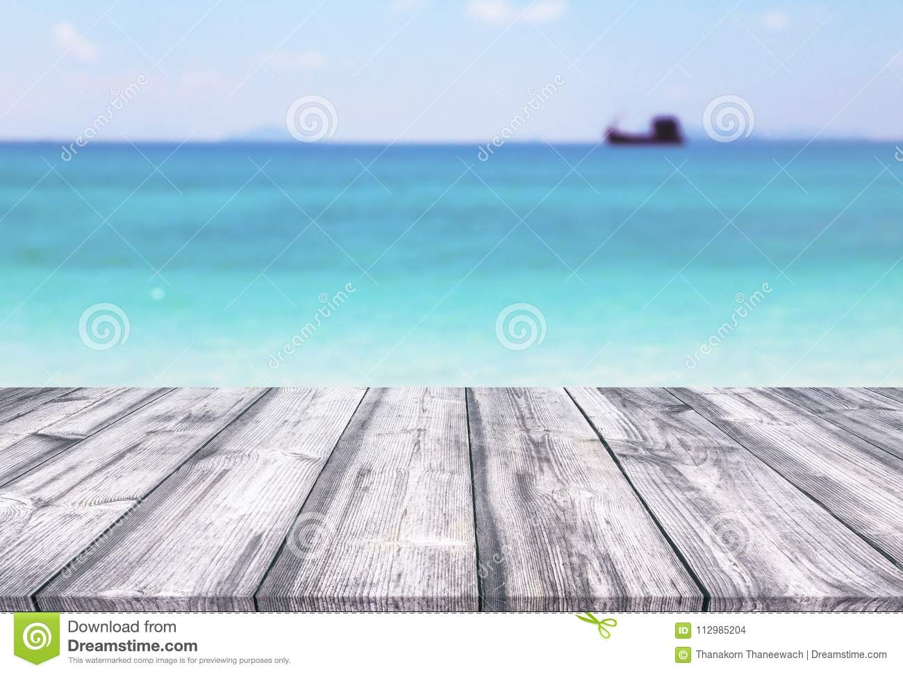 Wooden table with sky clouds and tropical sea background